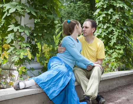 arbour: Young happy couple sits in the arbour twined greens