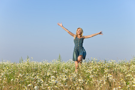 camomiles: The happy young woman jumps in the field  of camomiles Stock Photo