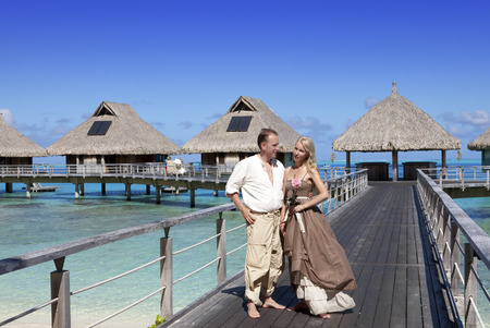 Lovers, man and woman on a wooden path at the sea, tropics photo