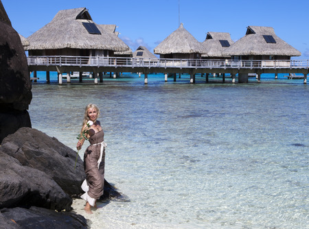 borabora: woman in a long dress with a rose in hand in the sea and traditional huts on  background