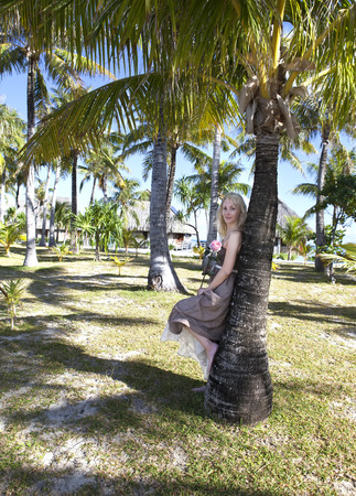 borabora: Young beautiful woman stands near palm tree Stock Photo