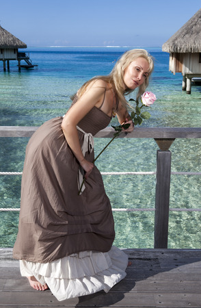 borabora: The beautiful woman in a long dress on the wooden bridge near the sea