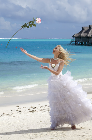 The happy bride in a white long dress throws up a rose on a beach on background of the sea photo