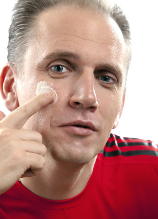 looking after: The mature man applies the cream which is looking after face skin