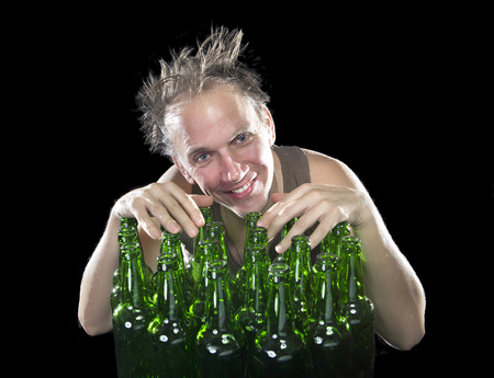 sobriety: The happy tipsy man near empty beer bottles Stock Photo