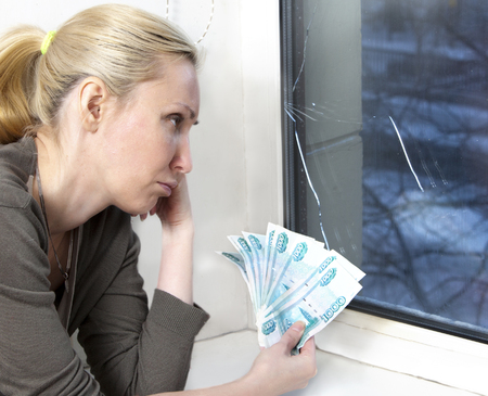 window repair: The sad young woman counts money for window repair with the burst, broken glass