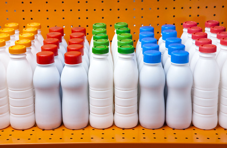 mass storage: dairy products bottles with bright covers on a shelf in the shop