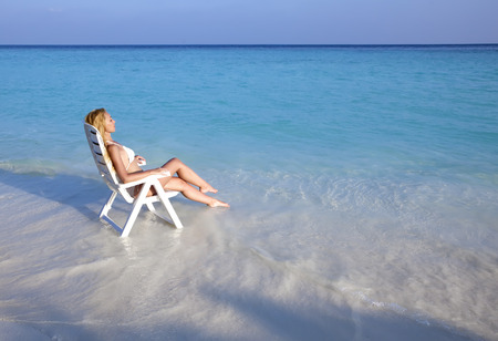 tans: Young pretty woman tans in beach chair in sea Stock Photo