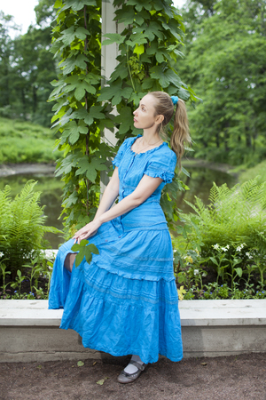 twined: The young beautiful woman in a blue dress in the arbor twined a green bindweed