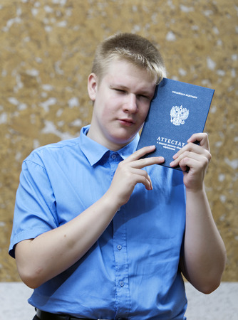 parting: schoolboy with the certificate about completion of education at school , upset from parting with school Stock Photo