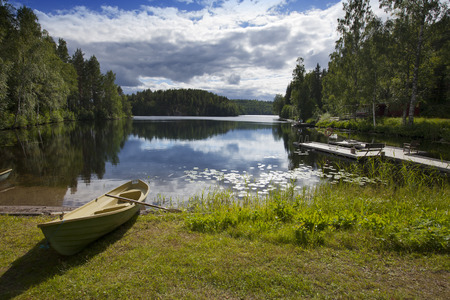 lake beach: Boat on the bank of the forest lake. Finland