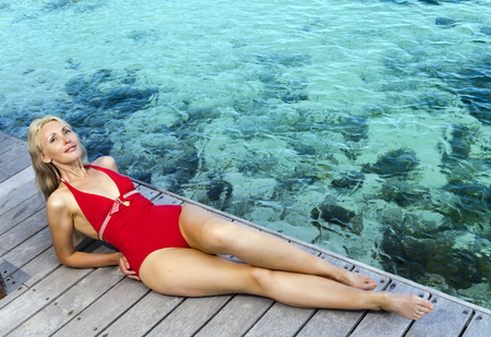 The young woman in a red bathing suit on sea background