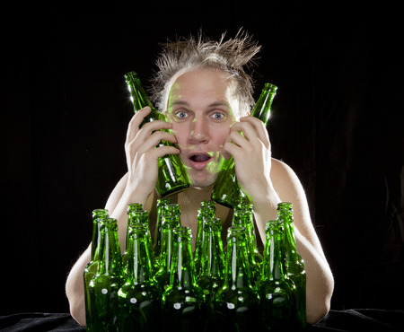 The tipsy man sits with a heap of beer bottles, a hangover Stock Photo