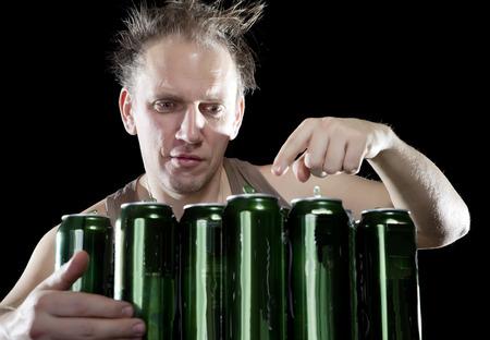 jarra de cerveza: Hangover.The hombre borracho y es un montón de latas de cerveza vacías Foto de archivo