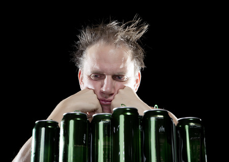 sobriety: Hangover.The drunk man and is a lot of empty beer cans Stock Photo