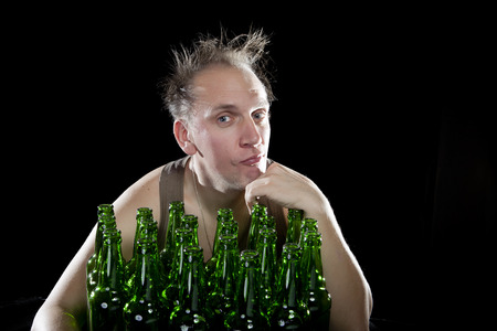 sobriety: The happy tipsy man near empty beer bottles Stock Photo