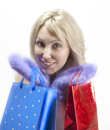 rejoices: The young woman in bright mittens with elegant packages rejoices to winter sale