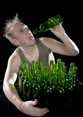 sobriety: The tipsy man sits with a heap of beer bottles, a hangover