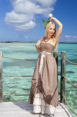 The beautiful woman in a long dress on a wooden platform over the sea Stock Photo