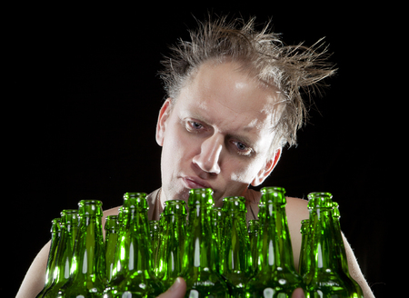 drunkenness: The tipsy man sits with a heap of beer bottles, a hangover