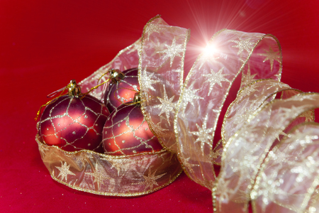 New Years composition on a red background - ball and ribbon