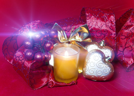 New Years composition on a red background - ball and ribbon and a candle Stock Photo