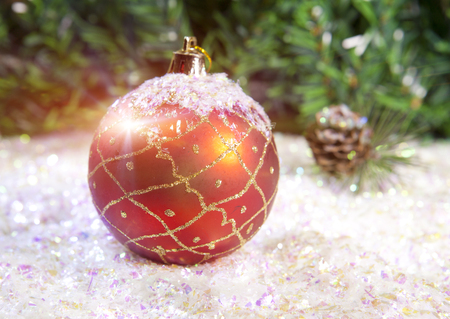New Years ball on a background of decorative snow and branch of a fir tree Stock Photo