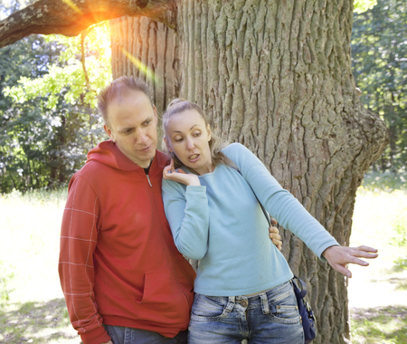 expressional: man and  woman near an oak in summer  day something was seen aside and looked scaredly and with astonishment