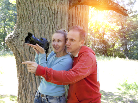 expressional: man and  woman near an oak in summer  day show to the side and photograph on the big camera Stock Photo