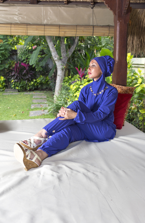 attractive woman in a Muslim swimwear burkini in gazebo for rest in a garden Stock Photo