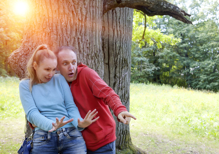 looked: man and  woman near an oak in summer  day something was seen aside and looked scaredly and with astonishment