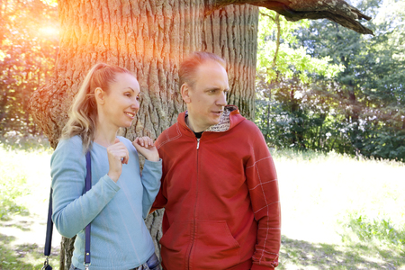expressional: man and  woman near an oak in summer  day something was seen aside and looked with a smile Stock Photo