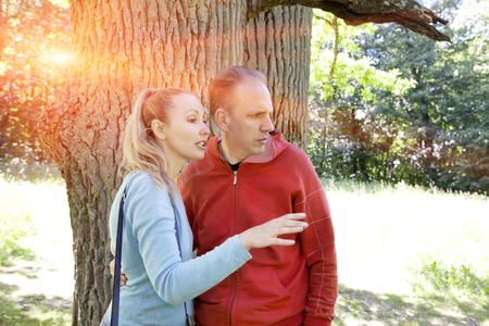 expressional: man and  woman near an oak in summer  day show to the side Stock Photo