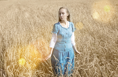 The beautiful woman in a blue long dress in the field of ripe cereals photo