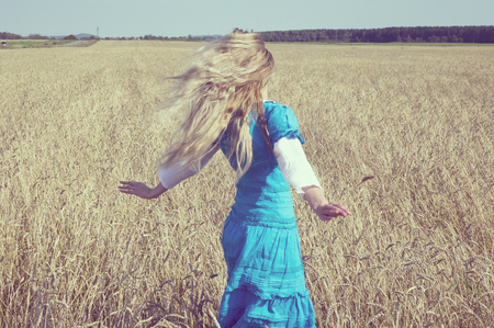 The beautiful woman in a blue long dress in the field of ripe ears of cereals, retro effect photo