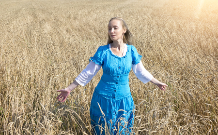 The beautiful woman in a blue long dress in the field of ripe ears of cereals photo