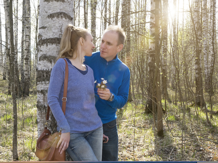 first day: The man gives to the woman a bouquet of snowdrops in a birchwood in the spring,