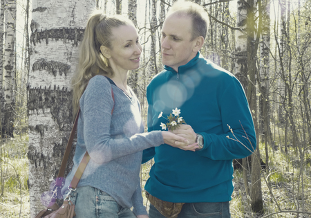 first day: The man gives to the woman a bouquet of snowdrops in a birchwood in the spring, toning