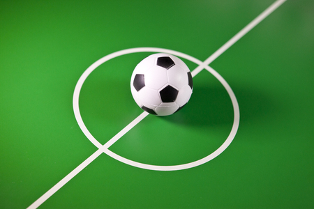 Toy soccer ball in a midfield, in the center of the green field