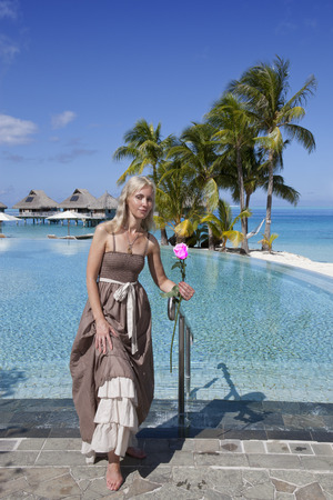 The woman in a long dress near the pool and palm trees Imagens