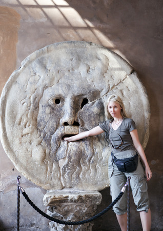 Italy. Rome. Woman tourist puts hand to mouth of truth