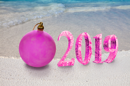 Christmas ball on the sandy seashore and the inscription 2019- New Year's card