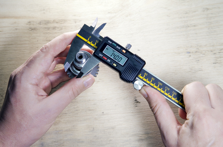 male hands with digital caliper