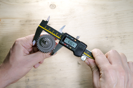 male hands with digital caliper