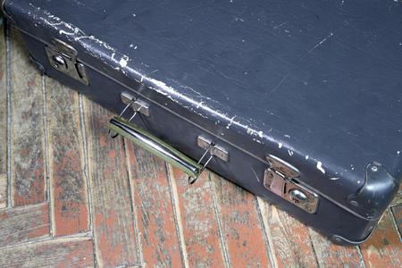 Vieille valise minable sur un plancher en bois