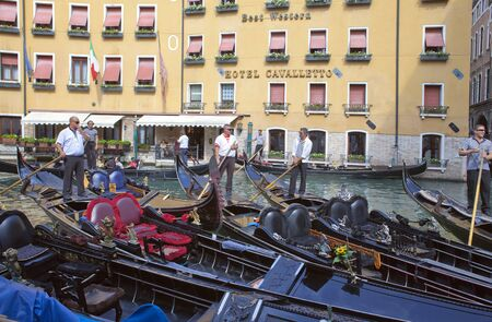VENICE, ITALY - SEPTEMBER 24, 2010: gondoliers at the gondolas waiting for passengers