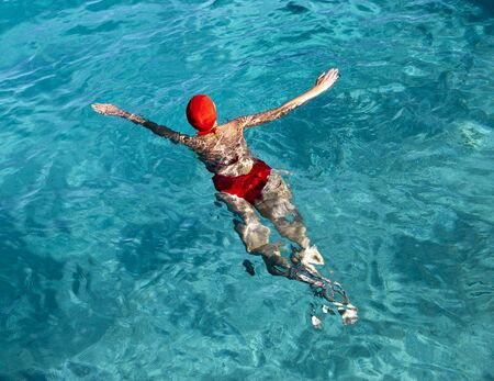young woman in a red bathing suit swimming in the blue sea in Tahiti
