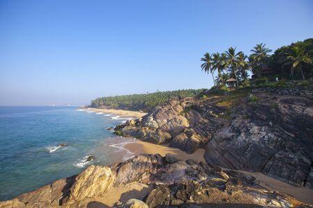 seashore with stones and palm trees. India. Kerala