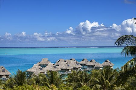 Blue lagoon of the Bora Bora island, Polynesia. Top view on palm trees, traditional lodges over water and the sea 版權商用圖片