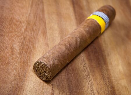 rolled cigar from a tobacco leaf on a wooden background, Small depth of sharpness Stock Photo